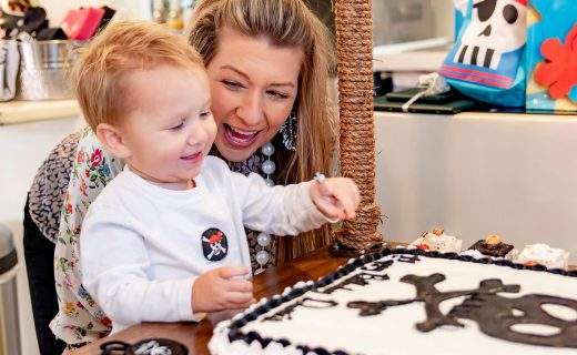 Toddler with his birthday cake and mom posing for a photo